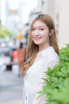Asian beautiful woman with long bronze hair wears white long sleeve shirt and smiles happily in an urban outdoor park while looking at the camera.