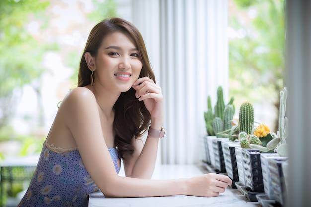 長い髪のアジアの美しい女性は、サボテンを持っているテーブルに彼女の手を置きます