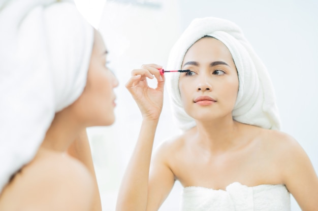 Asian beautiful women applying black mascara eyelashes after bathing