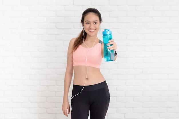 ヨガをした後、コピースペースのある白いレンガの壁の背景で水筒を持っているアジアの美しい女性。体重を減らし、柔軟性を高め、形を引き締めるための運動。