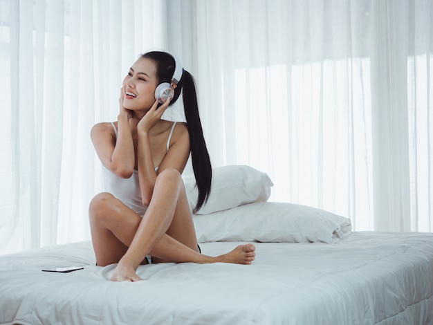 Asian beautiful women listening to music in bed