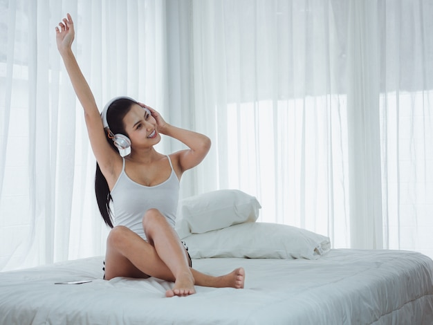 Asian beautiful women listening to music and stretching in bed