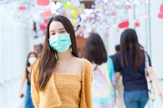 ヘルスケアの概念で医療マスクを身に着けている長い髪のアジアの美しい女性