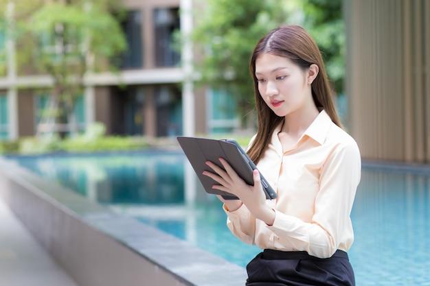 アジアの美しい働く女性は、タブレットまたはipadを使用して、どこからでも作業できるという概念でデータを検索します。
