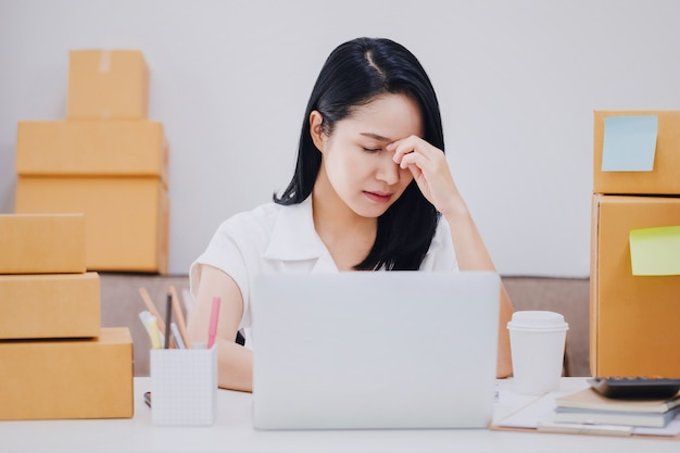 Asian beautiful young businesswoman feeling headache and stress in office space with product box.