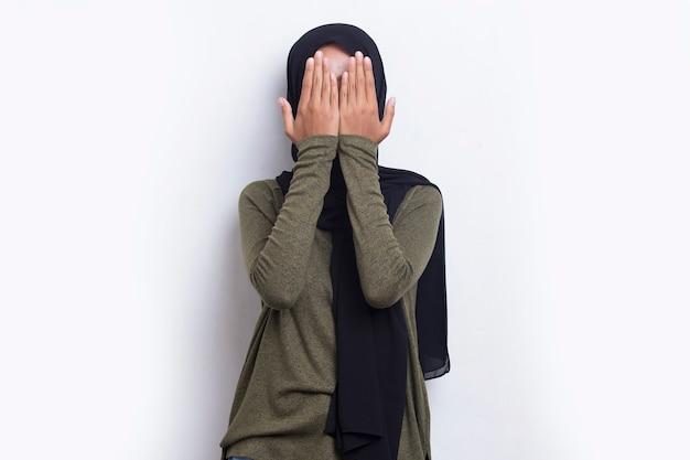 Азиатская красивая молодая мусульманская женщина закрывает лицо руками на белом фоне