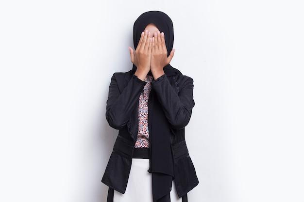 アジアの美しい若いイスラム教徒の女性は白い背景の上の彼女の手で彼女の顔を覆います