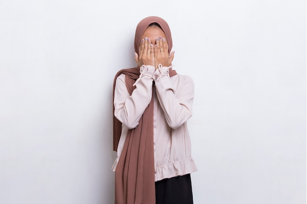 Asian beautiful young muslim woman covers her face with her hands on white background