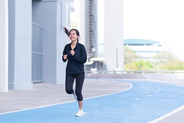 Азиатский красивый черный костюм молодой женщины с счастливым бегом или бегом на беговой дорожке.