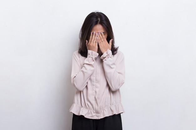 아시아의 아름다운 젊은 여성은 흰색 배경에 손으로 얼굴을 가린다