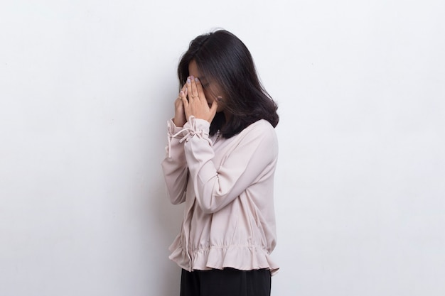 Asian beautiful young woman covers her face with her hands on white background
