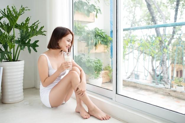 家でミルクを飲むアジアの美しい若い女性