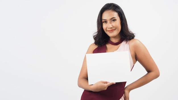 Азиатская красивая молодая женщина держа пустой чистый лист бумаги. студийный портрет с белым фоном. пустое место для текста. у нее загорелая кожа.