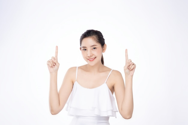 Asian beautiful young woman pointing both hand with finger on upper side with smile face