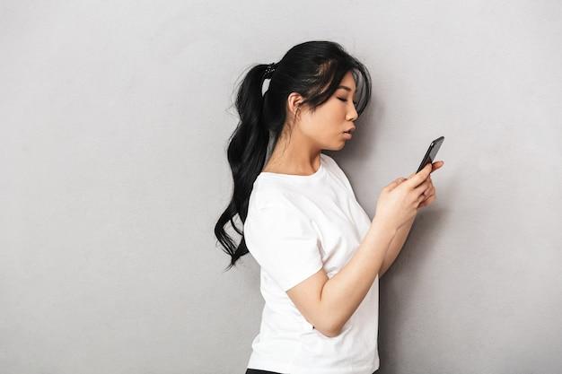 携帯電話を使用して灰色の壁を越えて孤立したポーズをとるアジアの美しい若い女性。