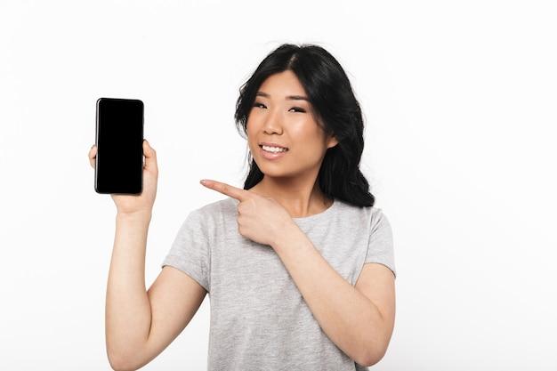 Азиатская красивая молодая женщина представляет изолированный над белой стеной показывая дисплей мобильного телефона.