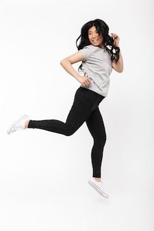 Asian beautiful young woman posing isolated over white wall   jumping.