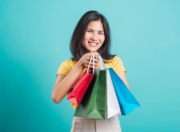 手に買い物袋を持っているアジアの美しい若い女性の笑顔