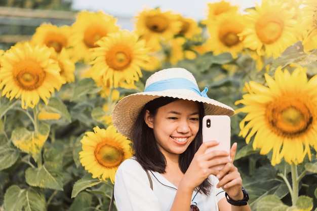 Asian beautiful young woman walking and take photo in sunflower field landscape background. concept of travel in summer season at thailand.