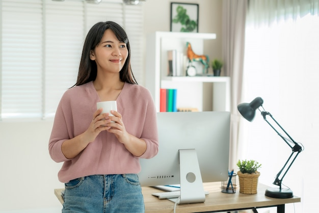 Asian beautiful young woman work from home working on computer and drinking coffee while relax from her work standing in living room at home.