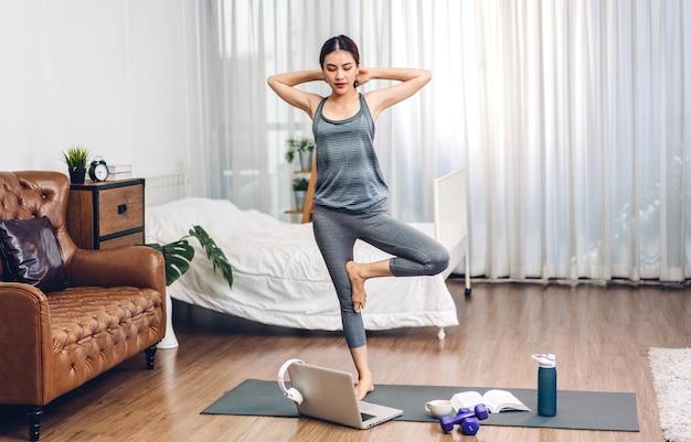 ヨガとフィットネスを練習するスポーツウェアのアジアの美しさの体のスリムな女性は、フィットネスと健康を行使します