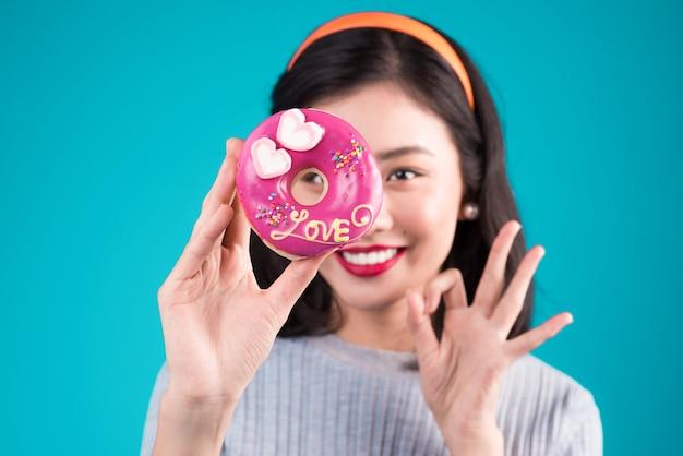 그녀의 눈에 핑크 도넛을 들고 아시아 아름다움 소녀. 과자, 파란색 배경 위에 서 있는 디저트와 함께 복고풍 즐거운 여자.