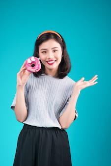 ピンクのドーナツを保持しているアジアの美女。お菓子、青い背景の上に立っているデザートとレトロな楽しい女性。
