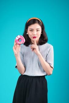 핑크 도넛을 들고 아시아 아름다움 소녀입니다. 과자, 파란색 배경 위에 서 있는 디저트와 함께 복고풍 즐거운 여자.