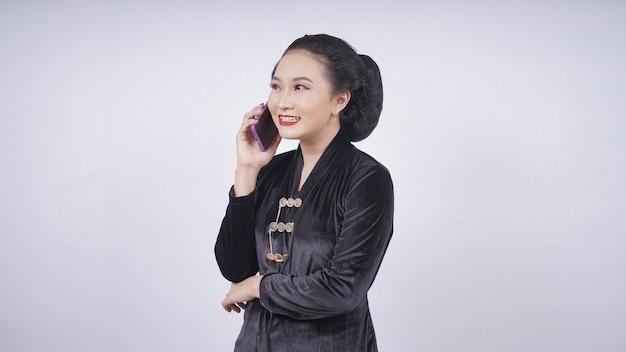 Азиатская красавица в кебая разговаривает по телефону на белом фоне