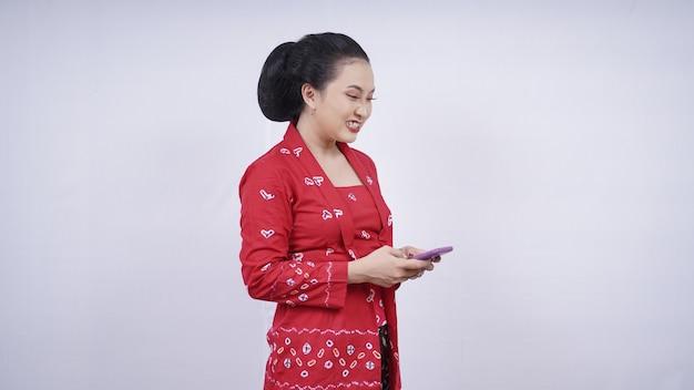흰색 배경에 격리된 역겨운 스마트폰 화면을 보고 있는 케바야의 아시아 아름다움
