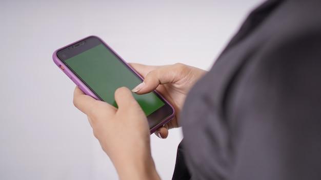 Азиатская красавица в кебая играет с мобильным телефоном на белом фоне