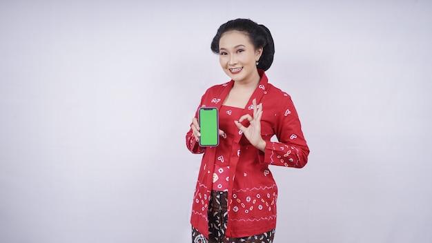Азиатская красавица в кебая показывает жест экрана смартфона нормально, изолированные на белом фоне