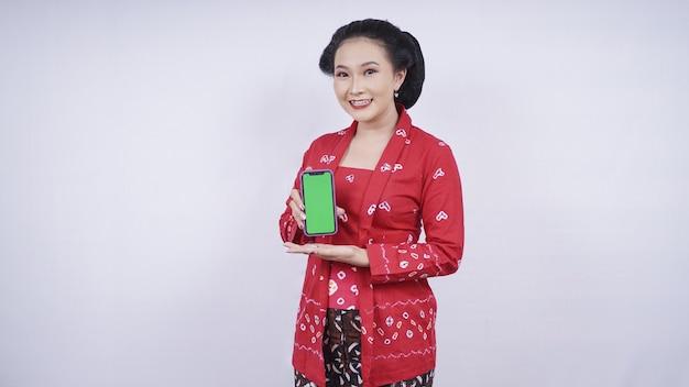 Азиатская красавица в кебая показывает экран смартфона на белом фоне