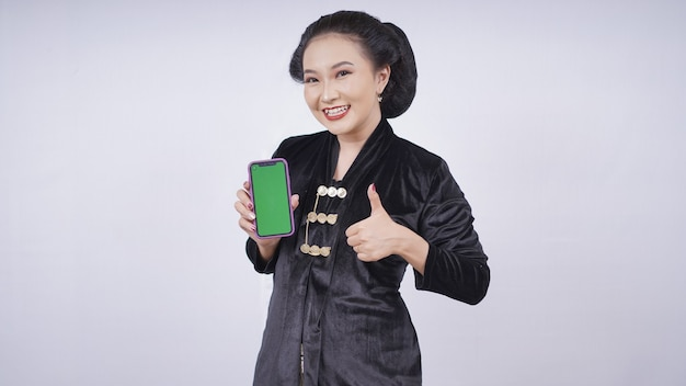 Asian beauty in kebaya showing smartphone screen ok gesture isolated on white background