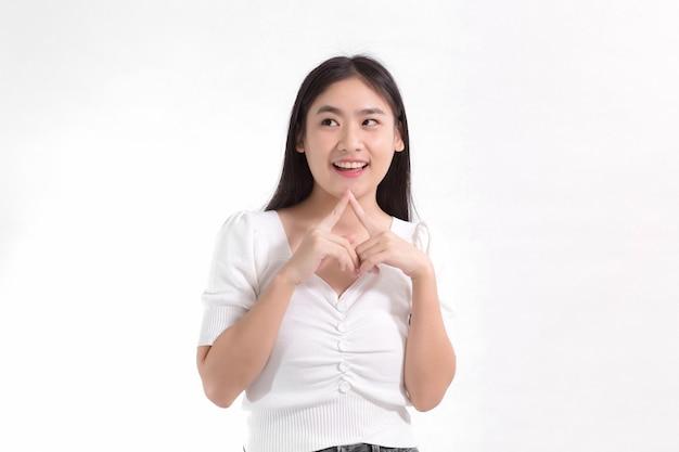 ピンクのドレスに笑みを浮かべて立っているアジアの美女が彼女の顔に触れながら何かを見ています