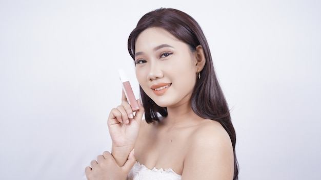 Asian beauty showing lipstick in her hand isolated on white background