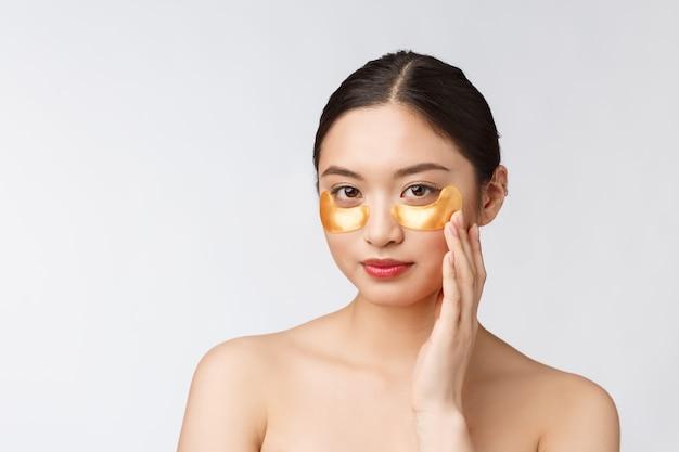 눈 아래 금 눈 마스크 패치와 함께 아시아 아름다움 십대 여자 케어 그녀의 피부