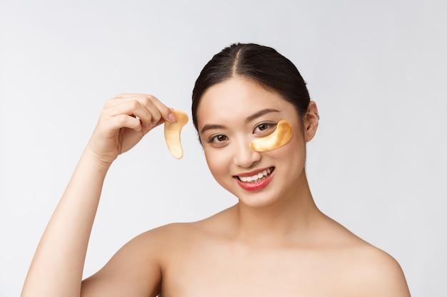 Азиатская красавица-подросток заботится о своей коже с золотыми глазными масками с заплатками под глазами