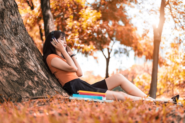 Asian beauty woman listen to the music in park. people lifestyles and entertainment concep