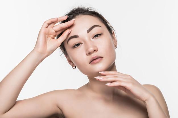 白い壁に分離されたアジアの美しさの女性のスキンケア