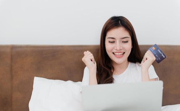 아시아 아름다움 여자는 신용 카드를 사용하여 인터넷을 통해 컴퓨터를 사용하여 구매합니다. 행복한 웃는 얼굴로, 가정에서 쇼핑 경험에서 새로운 정상적인 온라인 비즈니스가됩니다.