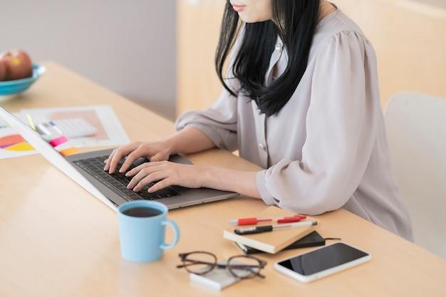 Азиатская черноволосая женщина работает дома с помощью ноутбука