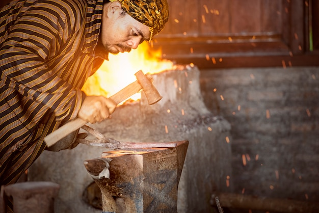 Asian blacksmith forging the molten metal with a hammer to make keris