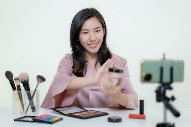 An asian blogger beauty blogger shooting a video of herself wearing an orange lipstick in a studio.