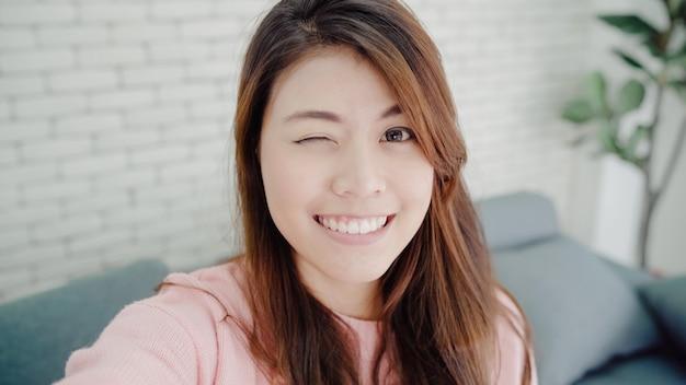 Азиатская женщина блоггер с помощью смартфона записи видео в блоге в гостиной дома