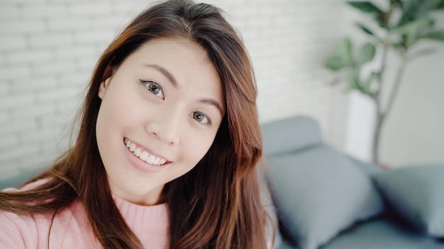Asian blogger woman using smartphone recording vlog video in living room at home