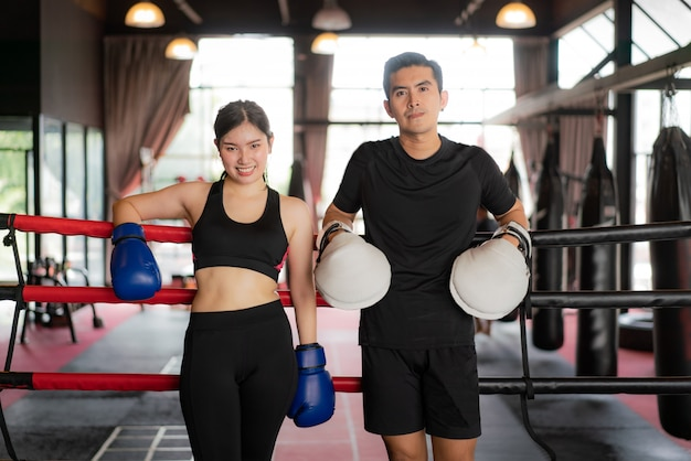 Asian boxer sports girl and trainer looking  smile while leaned on black red ropes on boxing ring.