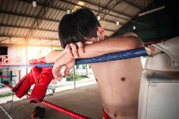 フェイスマスクを身に着けているアジアのボクサー。コロナウイルス病気