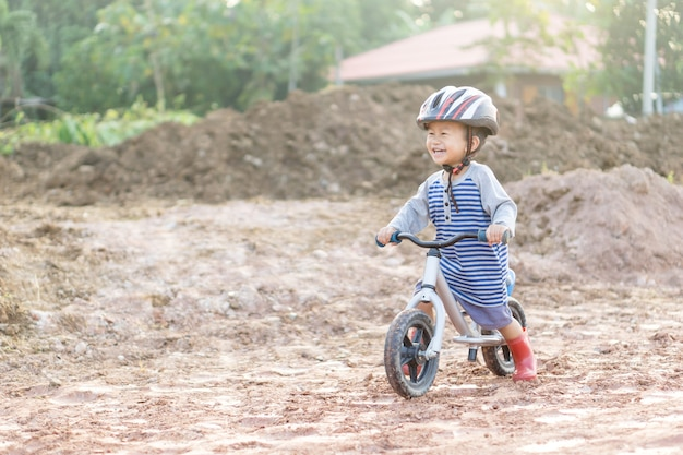 Asian boy about 1 year and 9 months is riding  baby balance bike on muddy construction road