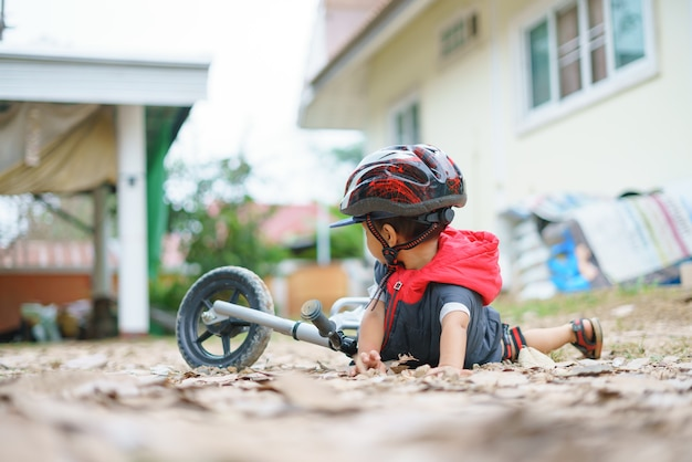 Asian boy about 2 years is riding baby balance bike and fall